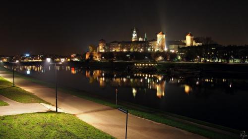 Zdjęcie zrobione z Mostu Grunwaldzkiego, licząc od pierwszego planu, znajdują się Bulwar Poleski, rzeka Wisła i wzgórze Wawel wraz z Zamkiem Królewskim i bazyliką archikatedralna św. Stanisława i św. Wacława.
